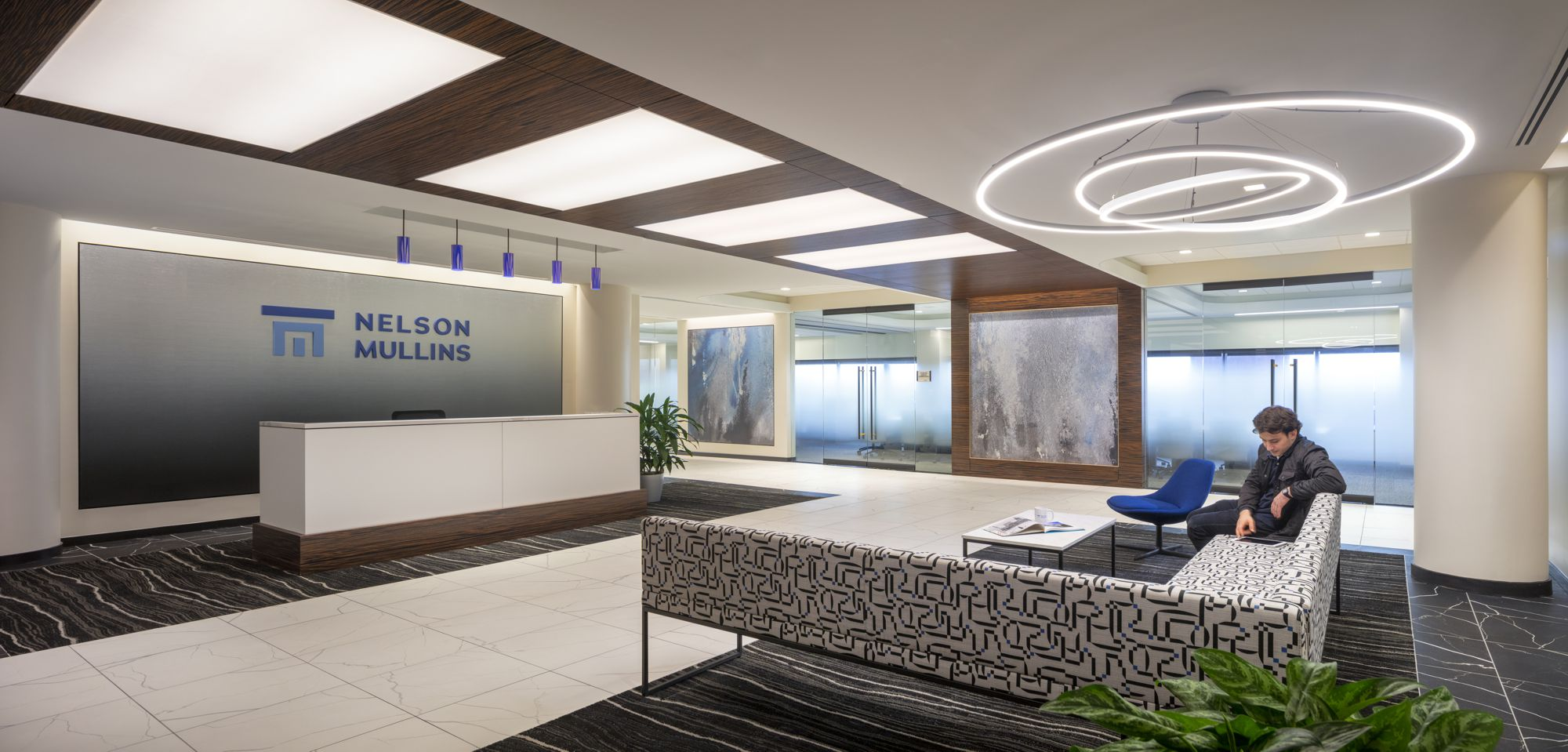 Stepping back to view the reception area, the royal blue accents pop in the lighting and firm logo.