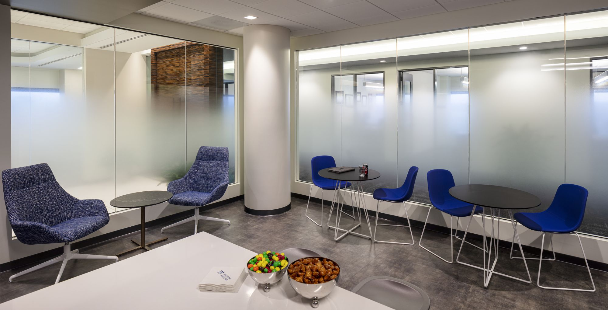 The lunch room ties in the bright blue accent color and utilizes a gradient film to enhance privacy.