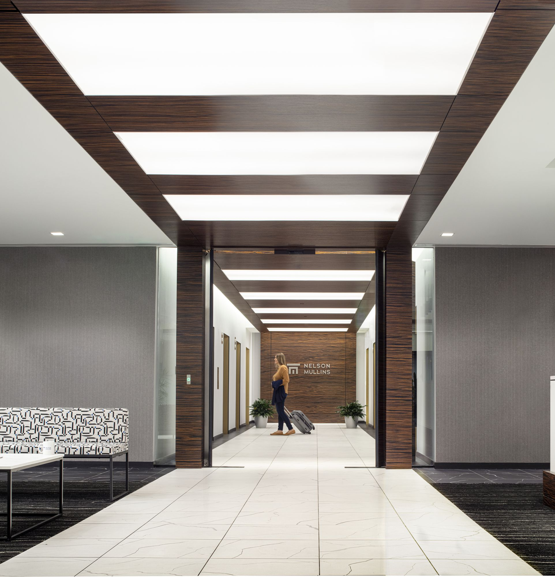 The lobby carries the ebony wood ceiling and backlit panels into the building core to reinforce the full-floor experience.