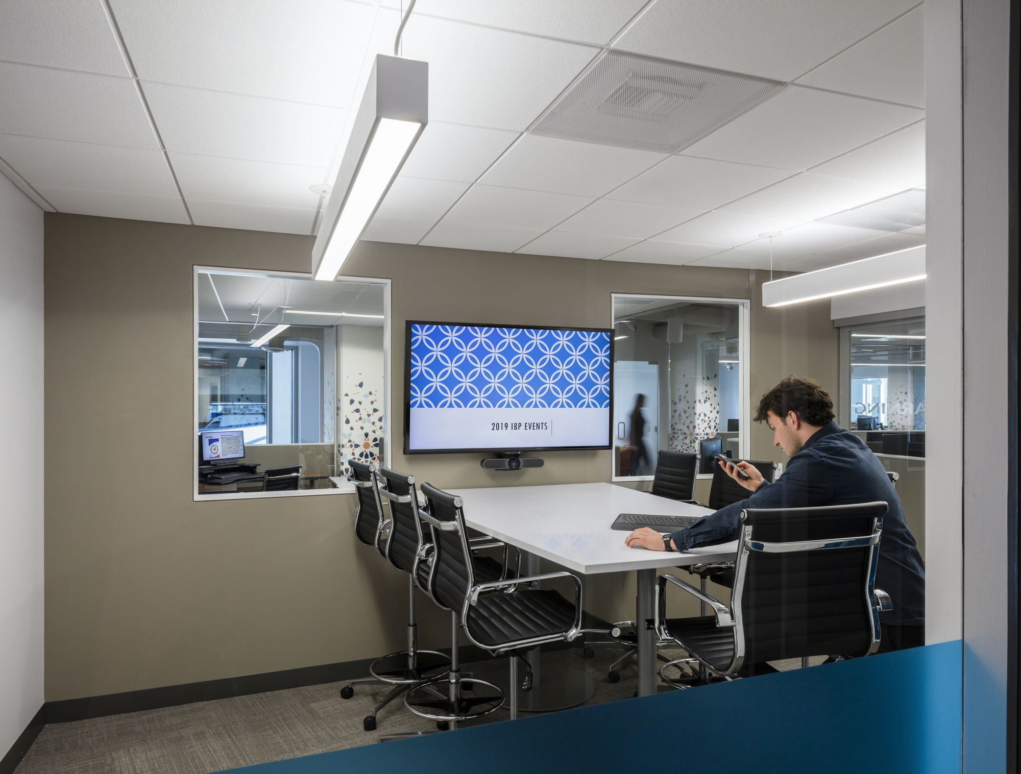 An interior meeting room along the corridor with aligned windows each side to allow focused views from interior out.
