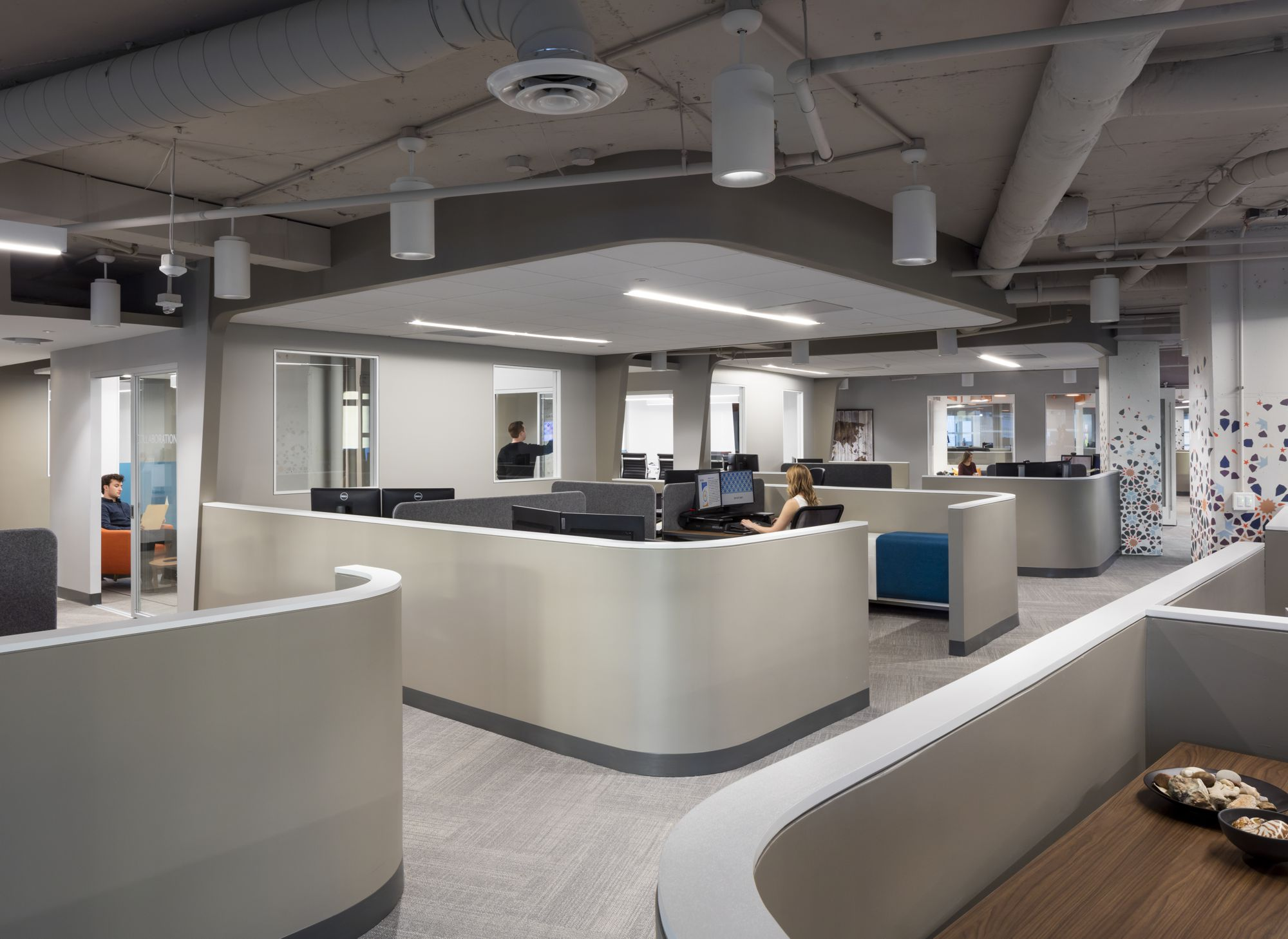 The open workstations are gathered into groups of 4 with dropped ceilings above for better acoustics, and to create a sense of place.  The curved walls create gracious circulation pathways through the area, but allow for greater distance between individual seats to allow for greater concentration.
