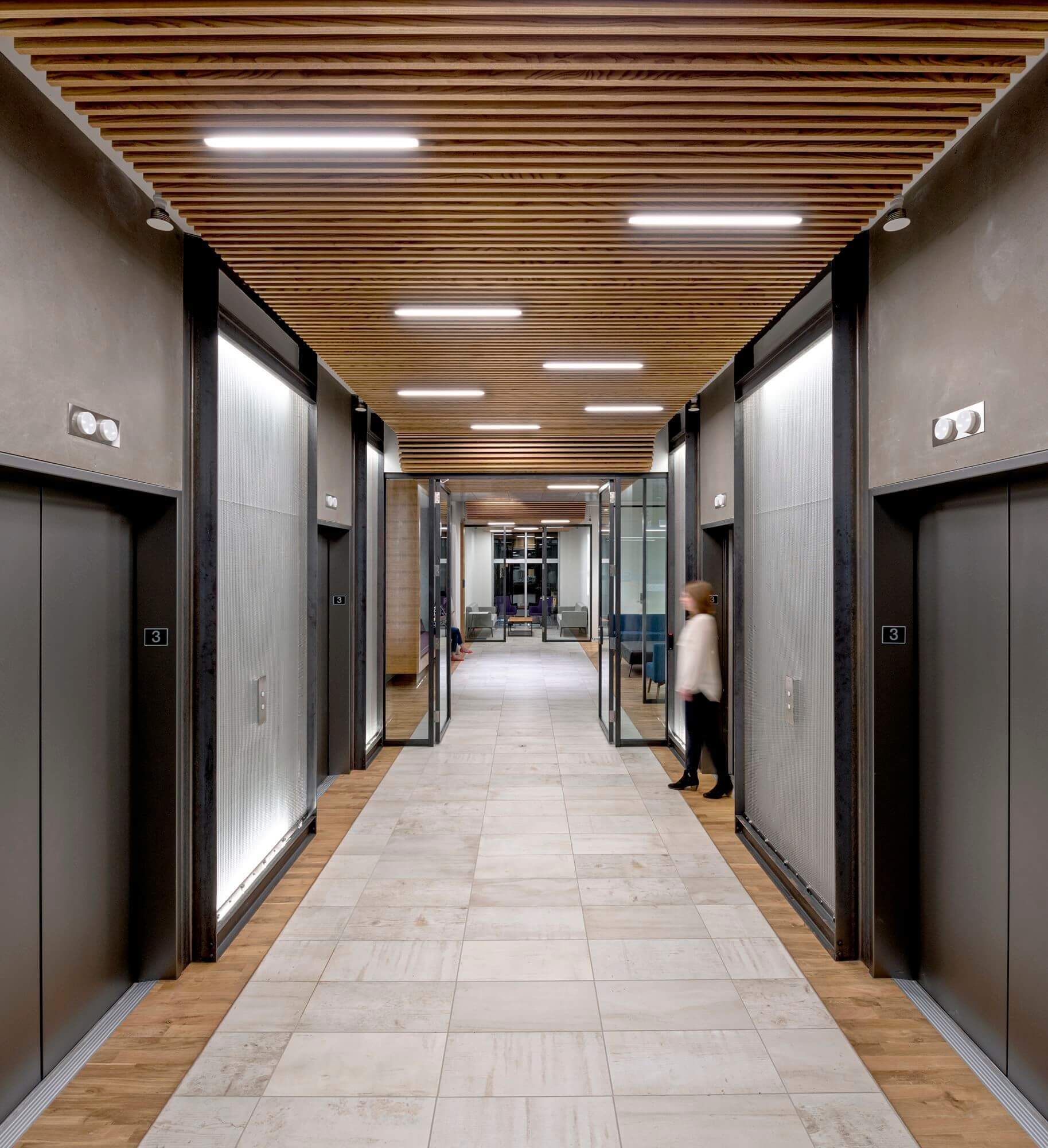 Steel, concrete, wood and glass create a warm industrial feeling throughout, and connect key design elements.  The wood from the historic stair is modernized in new wood flooring in the major circulation corridors, while the steel pipes are echoed in the elevator lobby framing and steel storefront glazing.