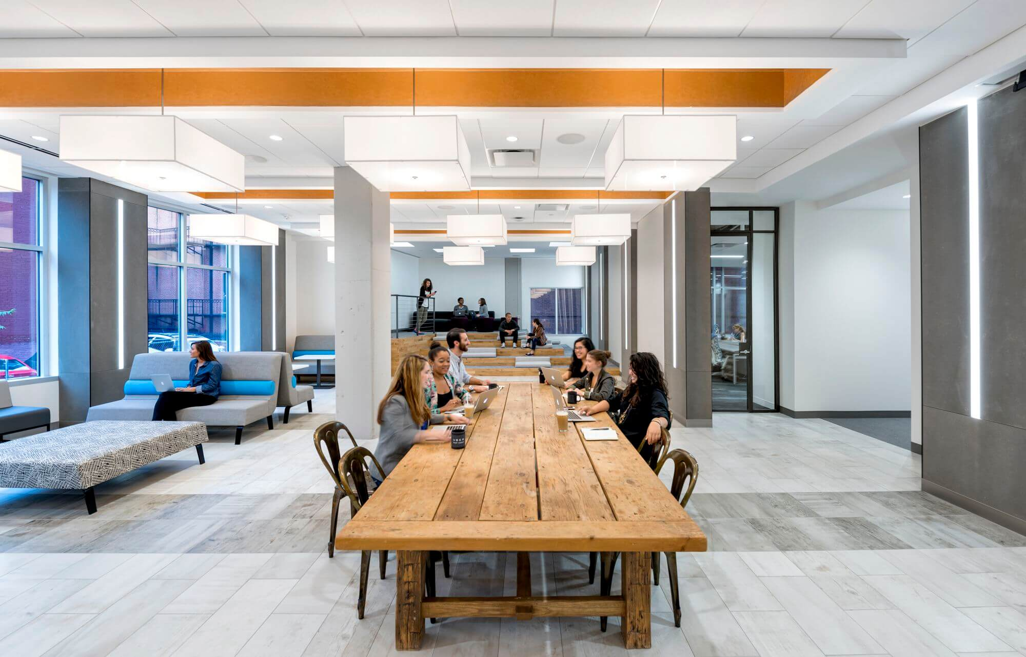 The project provides a lunch room featuring riser style seating and a communal table constructed from the floor joists salvaged from the townhouses.  The fully suspended reception desk brings together the steel, concrete and glass elements.
