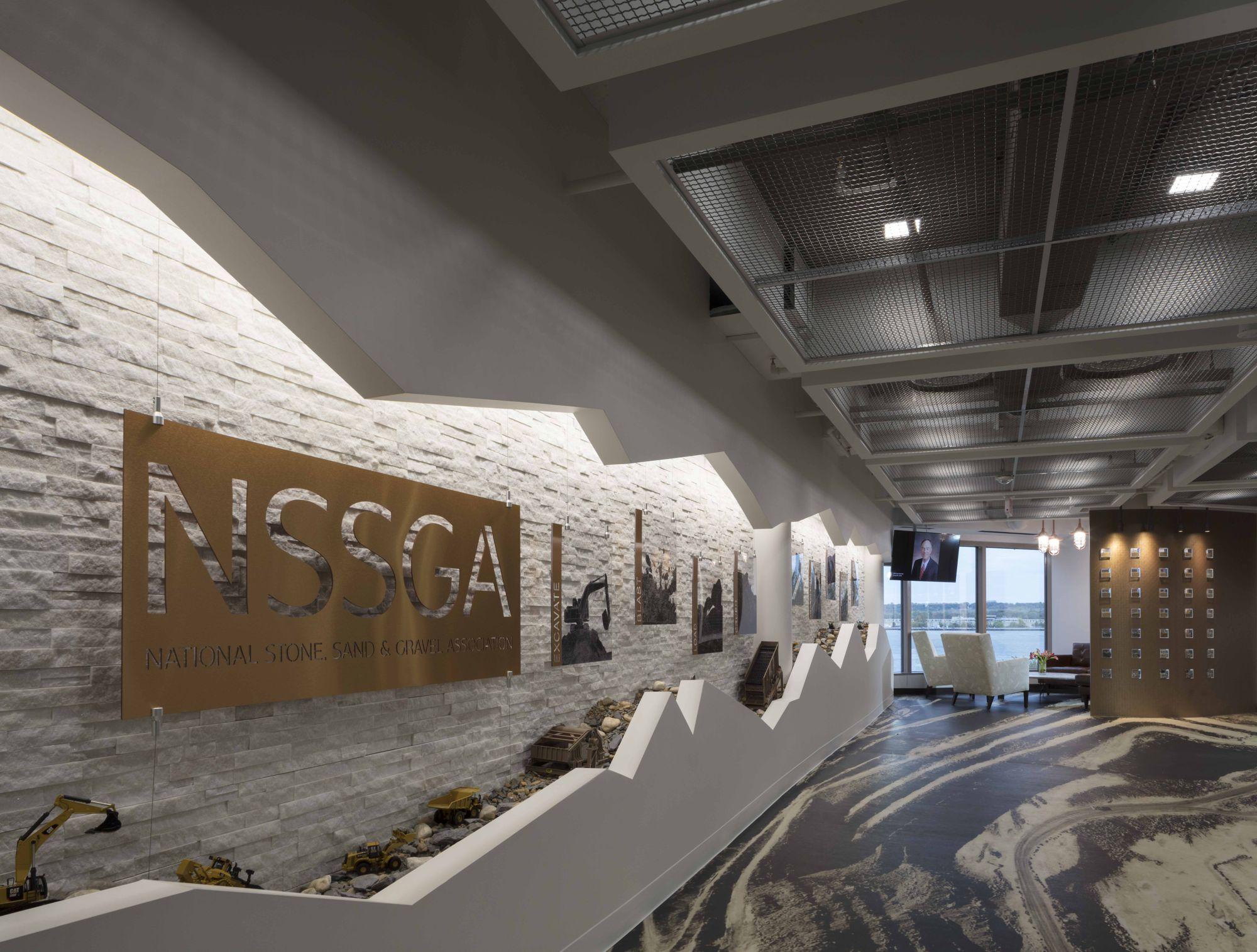 The flooring in the reception is an aerial view of a quarry; stone is the backdrop for the equipment model showcase on a gravel bed. Ceiling panels were created from metal mesh sifter material.