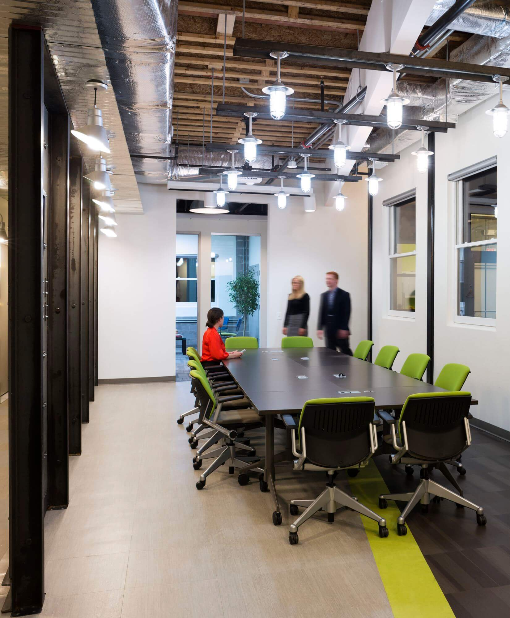 The fourth floor represents the future of American manufacturing, incorporating bright green elements to reflect a sustainable economy.  Steel was used to create custom pendant lighting in the primary meeting space, while sprinkler pipes support the cantilevered quartz coffee bar.