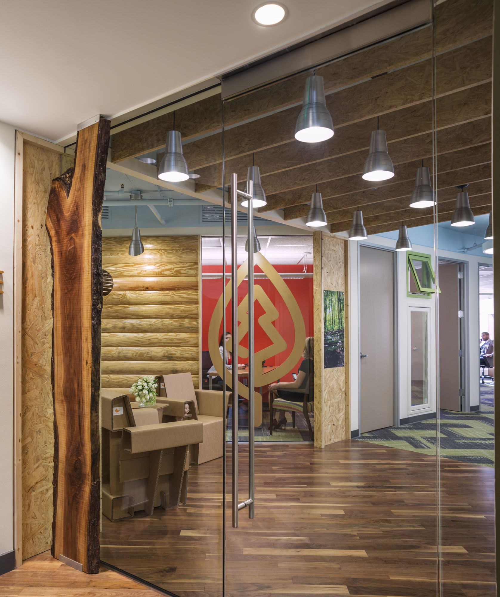 The live-edge wood framed entry, custom-designed MDF logo and custom SFI-sourced cardboard chairs and cardboard pendant lighting, invite visitors into a reception that emphasizes the beauty and diversity of sustainable wood products.